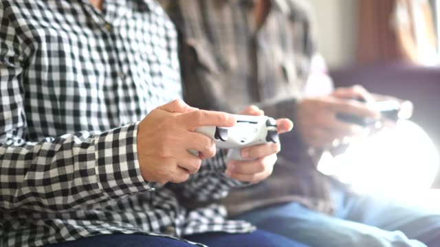 Male-and-female-hands-playing-video-game-at-home