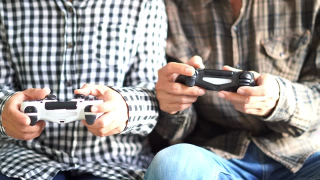 Male-and-female-hands-playing-video-game-at-home-Shooting-and-controlling-using-the-game-controller
