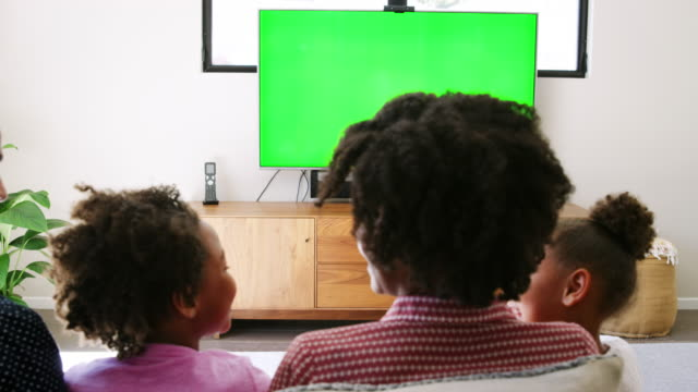 Rear-view-of-young-family-sitting-on-sofa-at-home-and-watching-television