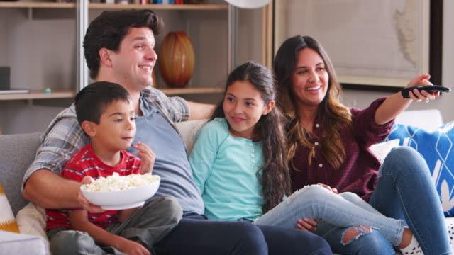 Familia-sentada-en-el-sofá-viendo-TV-y-comiendo-palomitas-de-maíz-juntos