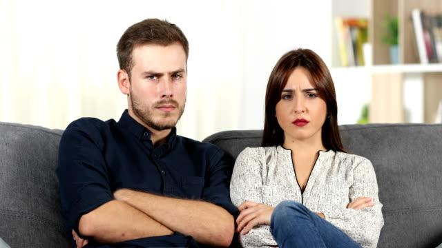 Enojado-pareja-discutiendo-sentados-en-un-sofá-en-casa