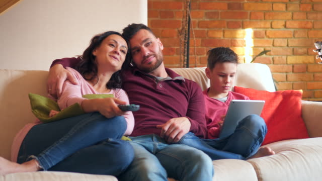 Parents-watching-tv-while-son-using-digital-tablet-at-home