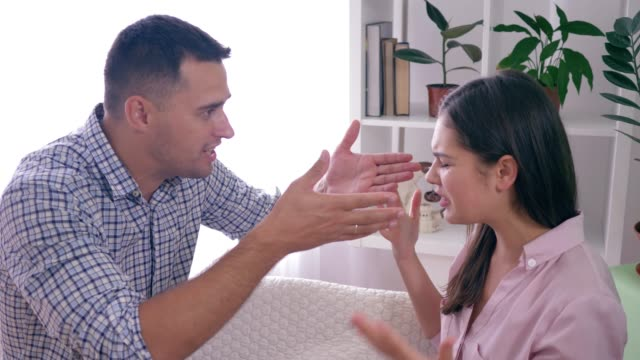 emotional-furious-girl-quarrels-with-boyfriend-and-Aggressive-gestures-hands-during-dispute-indoors