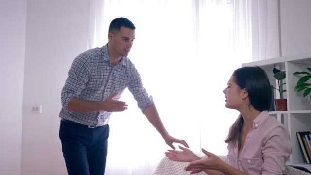 Angry-girl-with-boyfriend-scream-at-each-other-during-quarrel-and-furious-waving-hands-in-room