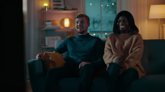 Happy-Diverse-Young-Couple-Watching-Comedy-on-TV-while-Sitting-on-a-Couch-they-Laugh-and-Enjoy-Show-Handsome-Caucasian-Boy-and-Black-Girl-in-Love-Spending-Time-Together-in-the-Cozy-Apartment-