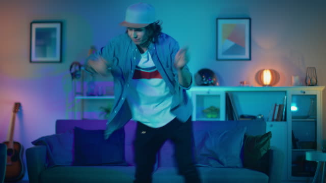Handsome-Excited-Hip-Young-Man-is-Dancing-in-the-Living-Room-while-TV-Plays-in-the-Background-He-is-Energetically-Moving-while-Screen-Adds-Reflections-on-Him-Cozy-Room-is-Lit-with-Warm-Neon-Light-