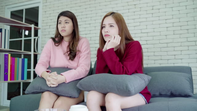 Lesbian-Asian-couple-crying-while-watching-drama-in-TV-in-living-room-at-home-sweet-couple-enjoy-romantic-moment-while-lying-on-the-sofa-when-relax-at-home-Lifestyle-couple-relax-at-home-concept-