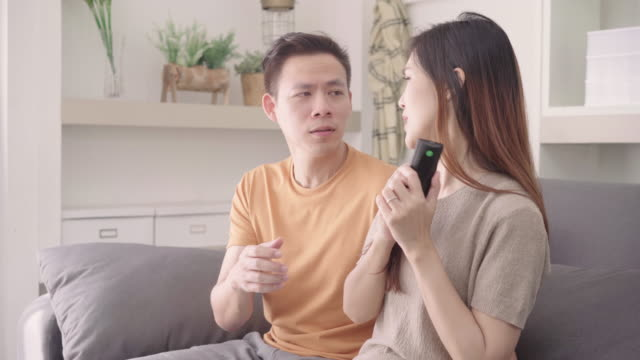 Asian-couple-argue-while-watching-TV-in-living-room-at-home-sweet-couple-have-angry-moment-while-lying-on-the-sofa-when-relax-at-home-Lifestyle-couple-relax-at-home-concept-