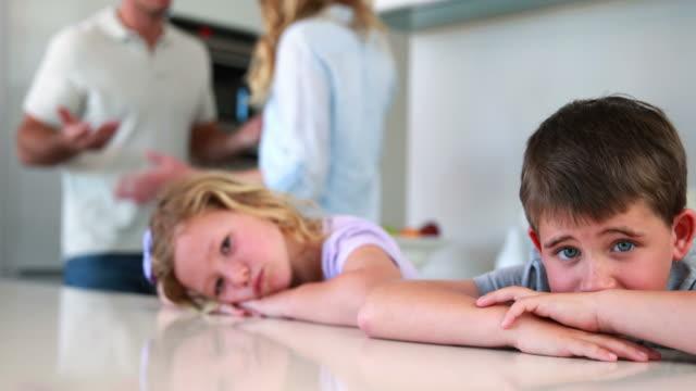 Pequeños-hermanos-bloqueando-ruido-de-padres-luchando-out