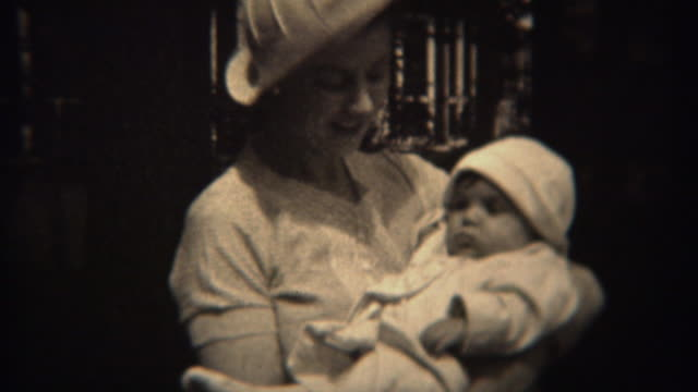 1937:-Mother-in-white-fashion-hat-holding-baby-daughter-in-matching-outfit-