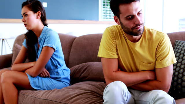 Couple-ignoring-each-other-in-living-room
