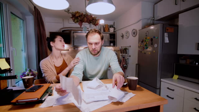 Worried-couple-looking-at-their-bills-in-the-kitchen-at-home-Man-and-woman-calculating-domestic-accounts