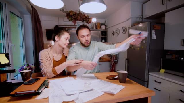Junges-Paar-Berechnung-Rechnungen-in-der-Küche-zu-Hause-Frau-versuchen-traurig-und-wütend-Mann-zu-beruhigen
