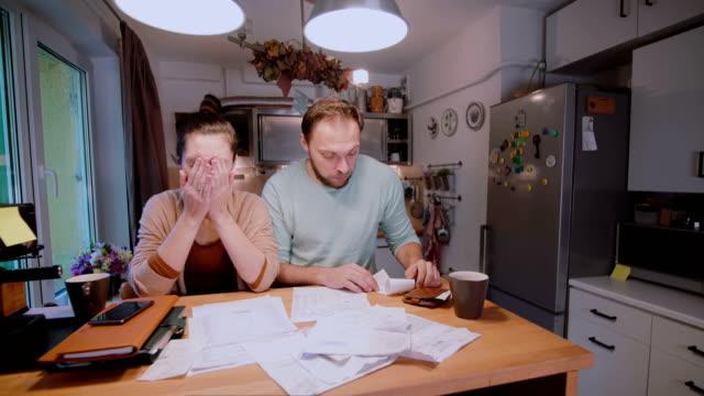 Pareja-joven-triste-pagar-las-facturas-Hombre-y-la-mujer-sentada-en-la-cocina-y-clasificación-de-cheques-y-cuentas-de