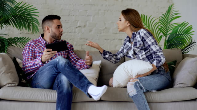 Young-upset-couple-quarrel-beacuse-of-man-have-internet-addiction-and-his-girlfrieng-shout-on-him-trying-to-take-off-tablet-computer-at-home