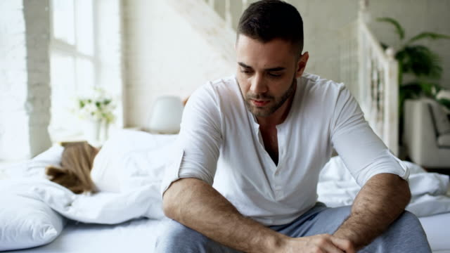Upset-young-man-sitting-in-bed-have-problems-with-sex-while-his-girlfriend-sleep-in-bedroom-at-home