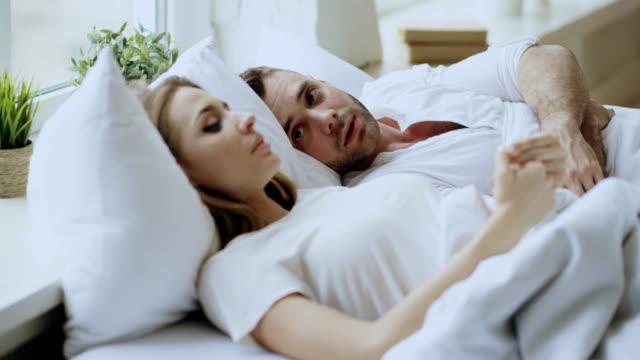 Acercamiento-de-pareja-con-problemas-de-relación-emocional-conversación-mientras-se-está-acostado-en-la-cama-en-casa-Gire-a-la-joven-a-su-novio
