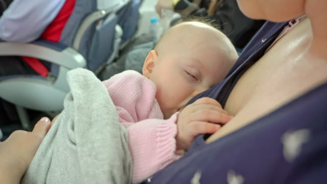 A-Woman-Breastfeeding-her-Child-on-a-Plane