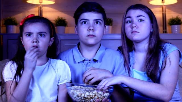 Niños-viendo-una-película-de-terror-en-la-TV