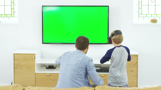 Father-And-Son-Play-Computer-Game-Using-Virtual-Reality-Headset