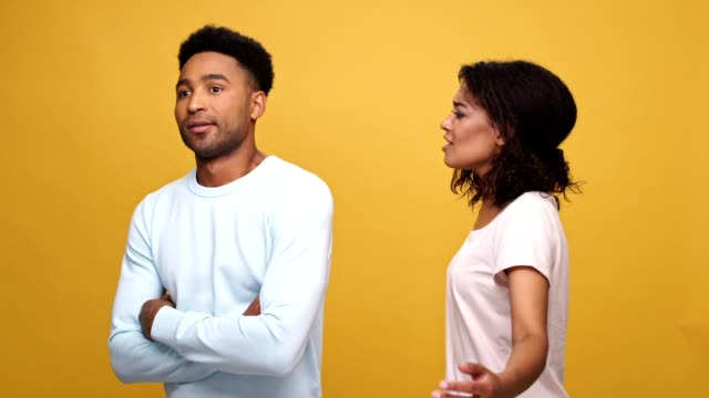 Young-afro-american-couple-having-a-fight-isolated-over-yellow-background