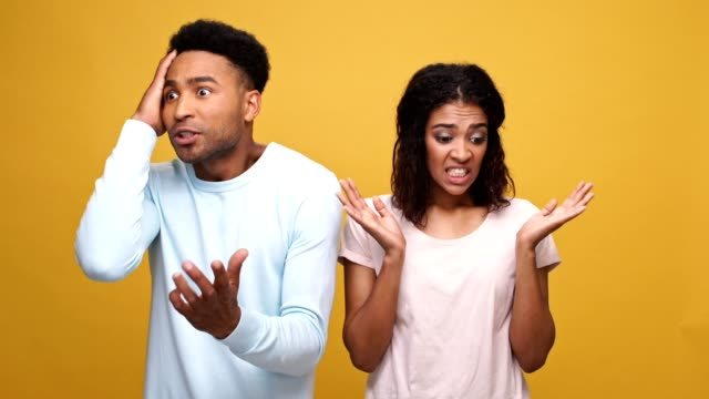 Frustrated-young-afro-american-man-having-a-disagreement-with-his-guilty-girlfriend-isolated-over-yellow-background