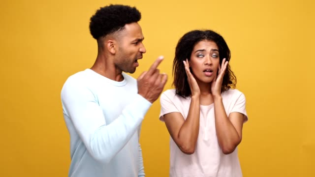 Young-african-couple-having-a-conflict-woman-is-closing-her-ears-with-hands-isolated-over-yellow-background