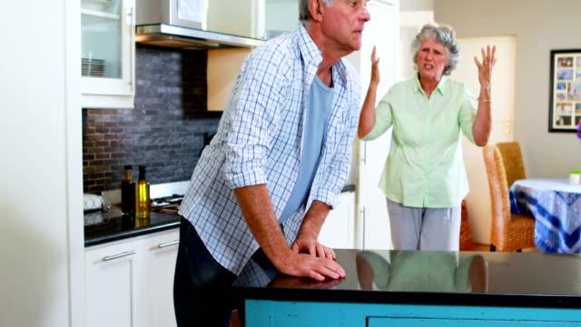 Frustrated-senior-woman-shouting-on-man-in-kitchen-4k