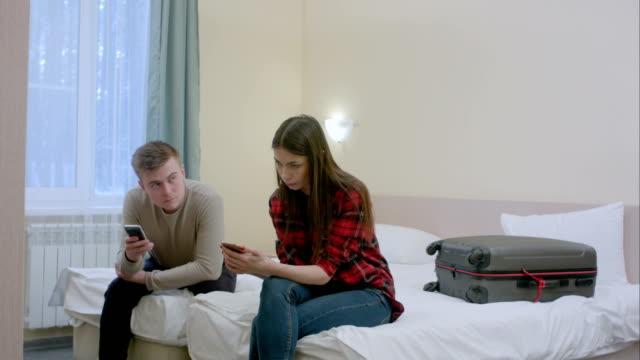 Pareja-sentada-en-la-cama-no-hablarse-después-de-la-pelea-escribiendo-sobre-smartphones