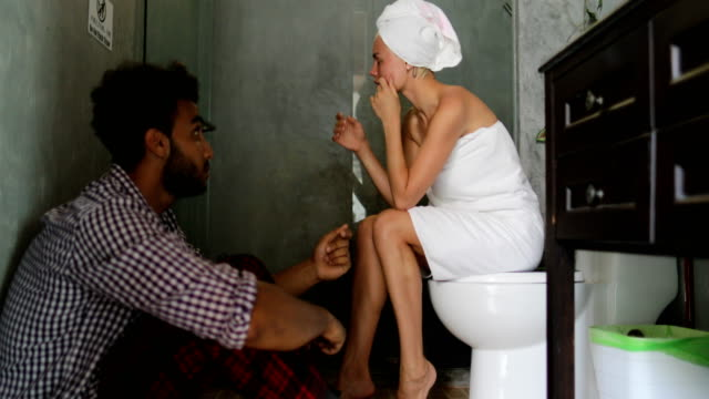 Young-Couple-Unhappy-In-Bathroom-Man-And-Woman-Arguing-Having-Problem-Girl-Crying-Sitting-On-Toilet-Guy-On-Floor
