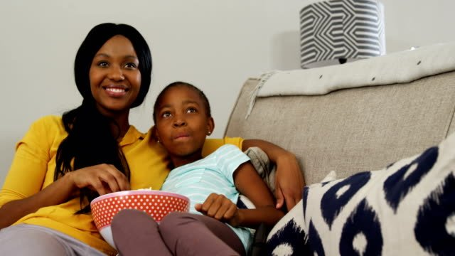 Mother-and-daughter-watching-television-in-living-room-4k