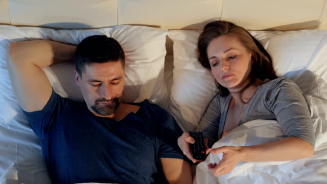 The-couple-quarreling-sharing-remote-control-watching-the-TV-