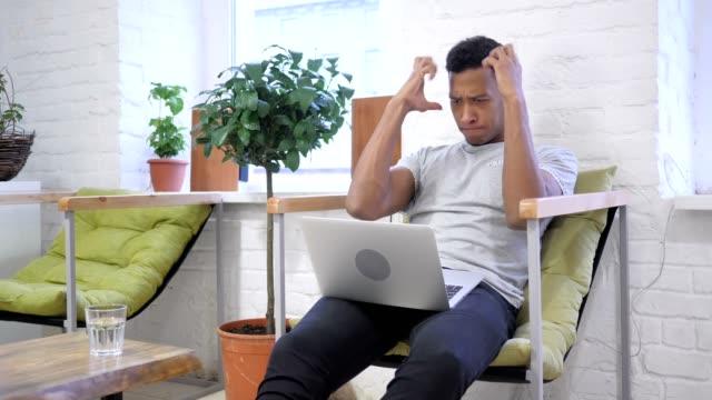 Angry-diseñador-africano-trabajando-en-ordenador-portátil-frustrado
