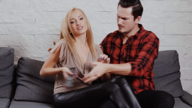 young-man-and-woman-are-sitting-on-the-couch-watching-TV-and-holding-a-remote