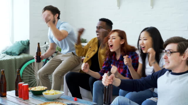 Multi-ethnic-group-of-friends-sports-fans-watching-sport-event-on-TV-together-eating-snacks-and-drinking-beer-at-home-on-holidays