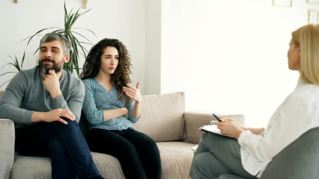 Pareja-joven-visita-la-oficina-del-profesional-psicólogo-Mujer-rizada-airadamente-discutiendo-y-hablando-de-su-novio-para-consejero-de-matrimonio