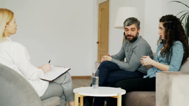 Mujer-enojada-discutiendo-y-hablando-de-su-marido-consejero-de-matrimonio-Pareja-joven-visita-oficina-de-profesional-psicólogo