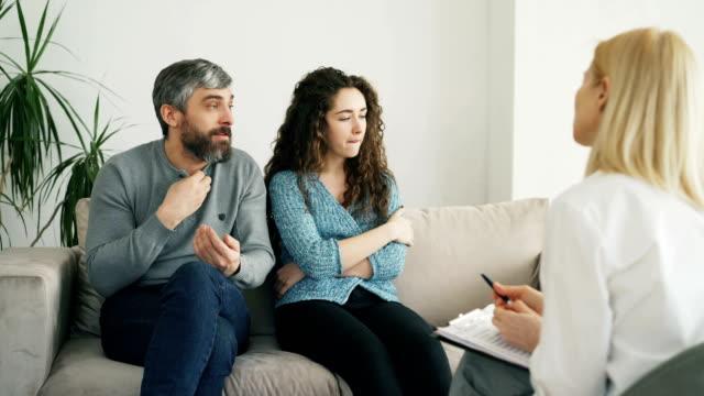Hombre-enojado-discutiendo-y-hablando-de-su-esposa-a-consejero-de-matrimonio-Pareja-joven-visita-oficina-de-profesional-psicólogo