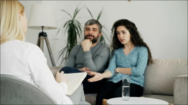 Cerca-del-profesional-psicólogo-escribir-notas-y-escuchar-pareja-joven-que-discutiendo-y-hablando-entre-sí