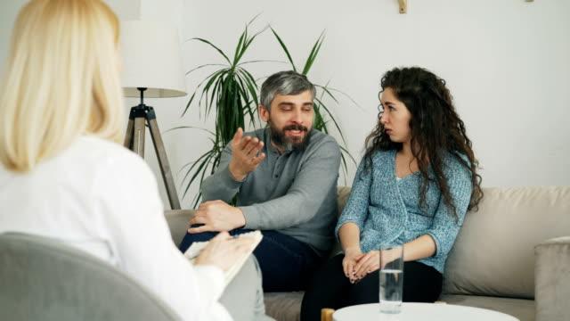 Matrimonio-argumentando-y-discutiendo-durante-visita-oficina-de-consejero-profesional-psicólogo-y-matrimonio