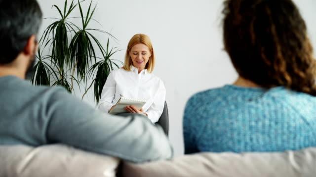 Mujer-profesional-psicólogo-hablando-escuchando-y-escribiendo-notas-en-el-cuaderno-mientras-que-discusión-pareja-visita-su-oficina-en-el-interior