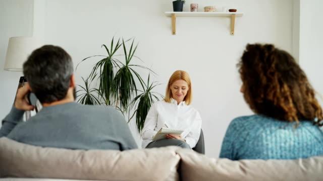 Mujer-profesional-psicólogo-escuchando-y-escribiendo-notas-en-el-cuaderno-mientras-joven-discutiendo-sobre-novio-hablando-por-teléfono-durante-visita-oficina-de-psicoterapia-en-el-interior