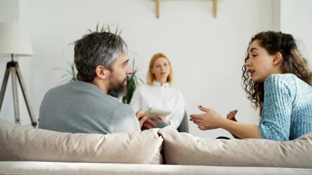 Mujer-psicoanalista-experimentado-escuchando-y-escribiendo-notas-mientras-que-enojado-matrimonio-argumentando-y-discutiendo-durante-visita-profesional-psicólogo-y-oficina-de-consejero-matrimonial