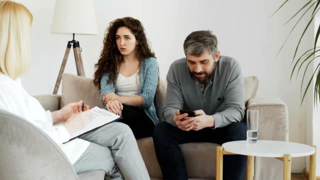 Mujer-profesional-psicólogo-escuchar-y-escribir-notas-mientras-joven-discutiendo-y-su-novio-Surfeando-en-smartphone-durante-visita-oficina-de-psicoterapia-en-el-interior