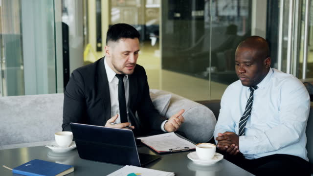 Angry-businessman-in-black-business-suit-criticizes-severely-his-african-american-employee-during-meeting-in-modern-cafe-Irritated-boss-gesticulates-emotionally-and-agressively-shout