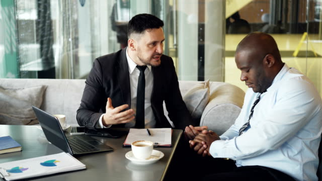 Irritated-bussinessman-in-suit-scolding-angrily-his-african-american-employee-in-shirt-at-modern-cafe-Angry-ceo-strikes-the-table-with-his-hand-nervously