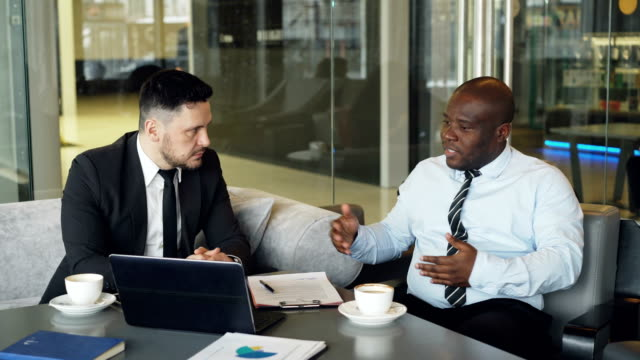 Angry-businessman-in-shirt-an-tie-criticizes-severely-his-partner-during-meeting-in-modern-cafe-Irritated-african-american-boss-gesticulates-emotionally-and-agressively-talking