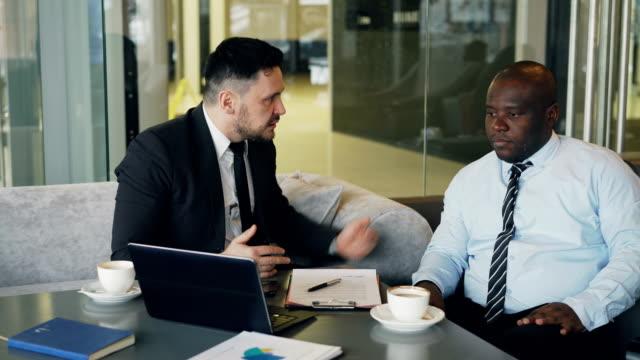 Wütend-Bussinessman-im-Anzug-schelten-seine-afroamerikanische-Mitarbeiter--und-packt-seine-Krawatte-zeigen-in-Vertrag-im-modernen-Café-scheitern-Wütend-Chef-auffällig-Tabelle-mit-seiner-Hand-nervös