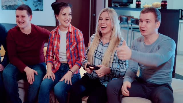 Happy-group-of-laughing-male-and-female-friends-playing-video-games-with-wireless-controllers