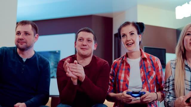 Empresa-feliz-de-los-amigos-de-relajarse-jugando-videojuegos-y-divertirse-interior-en-piso-moderno